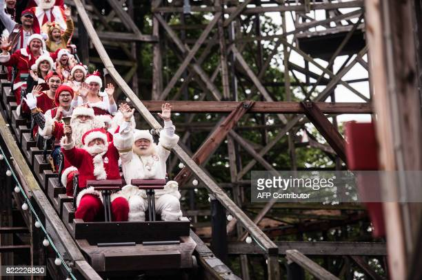 Santas take a ride in a rollercoaster at the amusement park Dyrehavsbakken in Klampenborg north of Copenhagen on July 25 2017 Since 1957 Santas from...