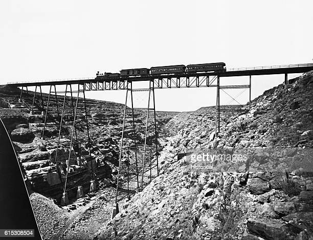 Sante Fe Railroad Bridge over Canyon Diablo, Arizona, showing train and signs of Albuquerque, New Mexico, clothing stores, etc., painted on Canyon...