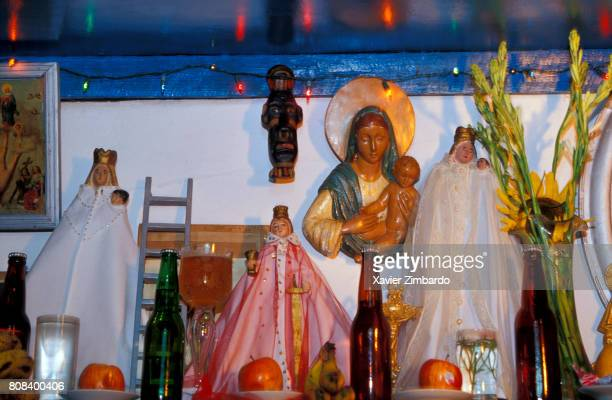 Santeria altar with statues of Virgin Mary and Jesus bottles of rum and beer candles apple fruits magic drinks on December 3 2002 at Guantanamo Cuba
