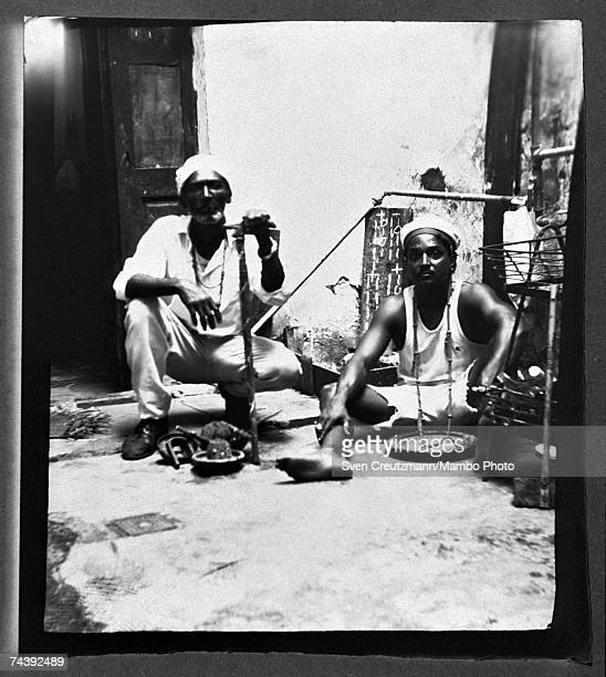 Santeria babalawo Juliano and priest Enrique pose on October 21 1998 in the old town in Havana Cuba Juliano holds a Baku and kneels in front of a...