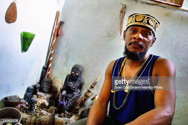 Santeria babalawo Victor Omolofaoro Betancourt President of the Association Ifa Iranlowo poses in front of his outdoor altar on January 19 2002 at...