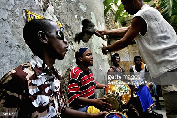Santeria believer touches the head of a drummer with a chicken to be sacrificed later during a ceremony performed for Fidel Castro's recovery from...