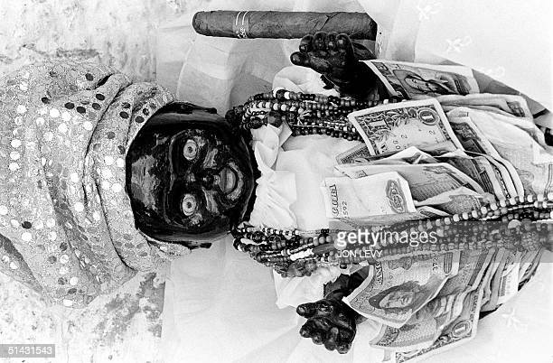 Santeria doll is decorated with offerings of beads money and cigar at a religious gathering of Catholics near Havana 12 December 1997 The AfrcanCuban...