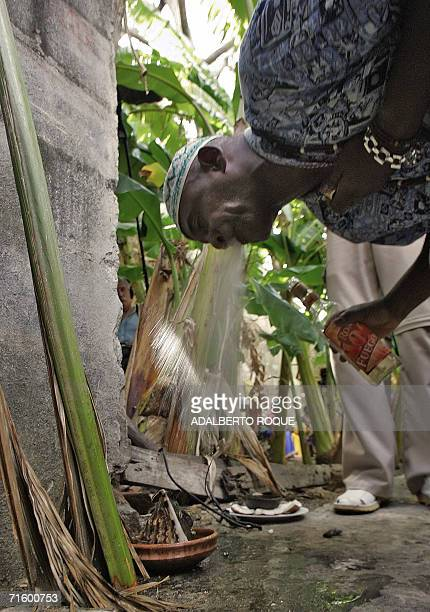 A santeria priest blows brandy over an Elegua as part of a prediction ritual asking for the health of Cuban President Fidel Castro 07 August 2006 in...