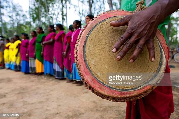 Santhal man beats a drum as women dance in the background The Santhal are the largest tribal community in India They have a distinct culture of their...