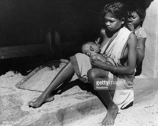 Santhal woman breastfeeding her baby while a little girl picks louse from her hair Cal TV Film Prod Centre