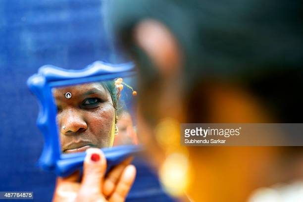 Santhali looks into a mirror after applying makeup during a festive celebration The Santhal are the largest tribal community in India They have a...