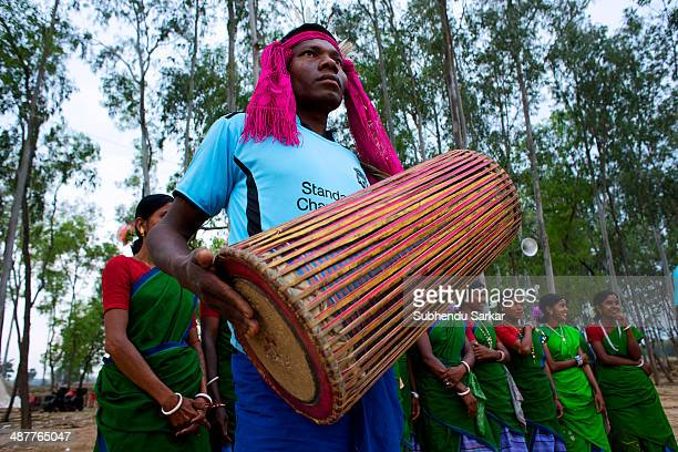 Santhali man plays a drum while women wait to begin dancing in the background The Santhal are the largest tribal community in India They have a...