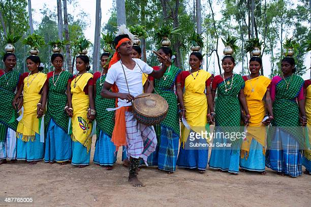 Santhali man plays drum as women perform a group dance The Santhal are the largest tribal community in India They have a distinct culture of their...