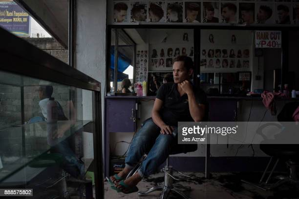 Santi a father of three and a gay beautician waits for customers inside a salon and barber shop where he works on November 24 2017 in Baloi town...