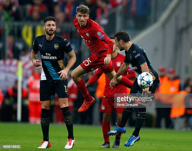 Santi Cazorla and Olivier Giroud of Arsenal challenges Thomas Mueller of Bayern Muenchen during the UEFA Champions League Group F match between FC...