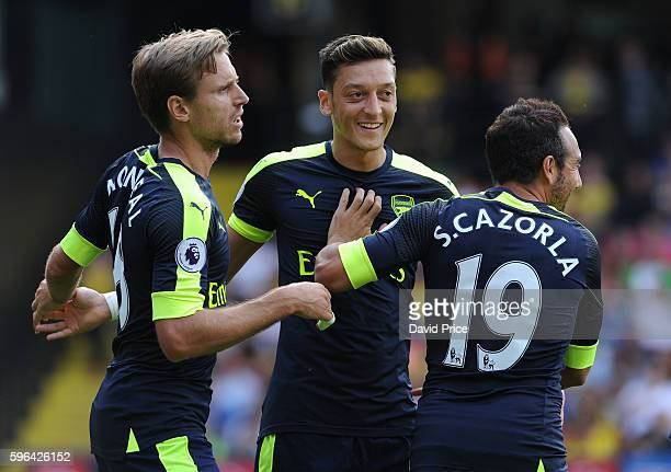 Santi Cazorla celebrates scoring Arsenal's 1st goal with Nacho Monreal and Mesut Ozil during the Premier League match between Watford and Arsenal at...