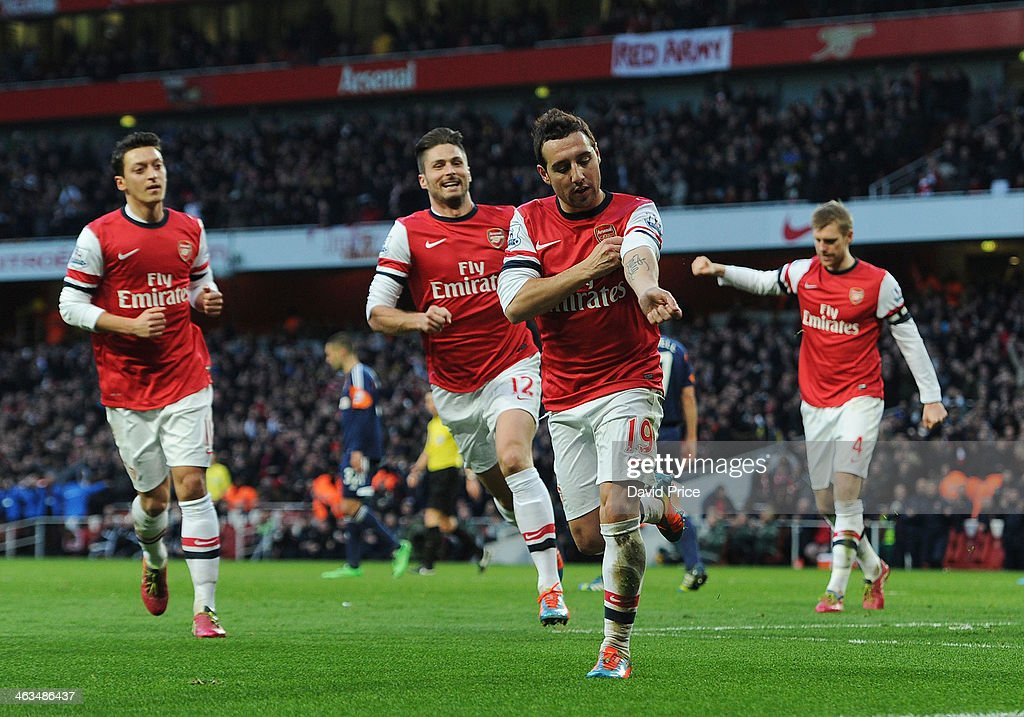 Santi Cazorla celebrates scoring his and Arsenal's 1st goal with Olivier Giroud and Mesut Oezil during the match between Arsenal and Fulham in the Barclays Premier League at Emirates Stadium on January 18, 2014 in London, England.