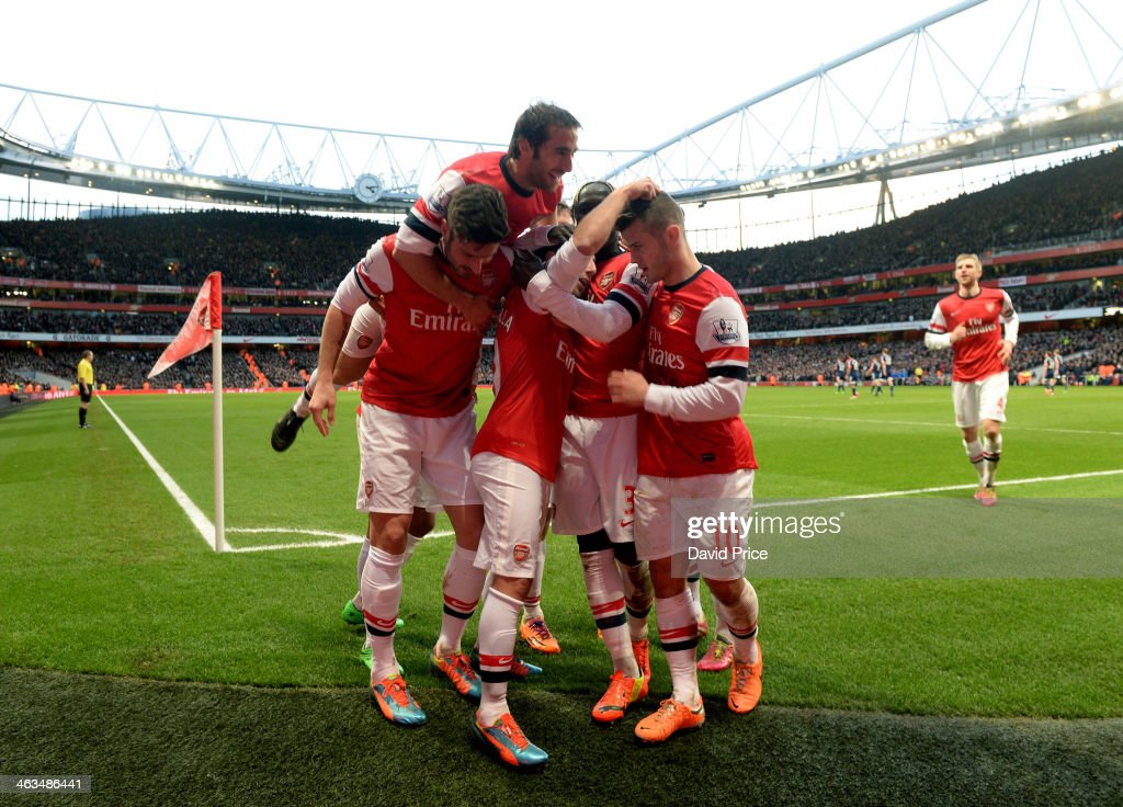 Santi Cazorla celebrates scoring his and Arsenal's 1st goal with Olivier Giroud, Mathieu Flamini and Jack WIlshere during the match between Arsenal and Fulham in the Barclays Premier League at Emirates Stadium on January 18, 2014 in London, England.
