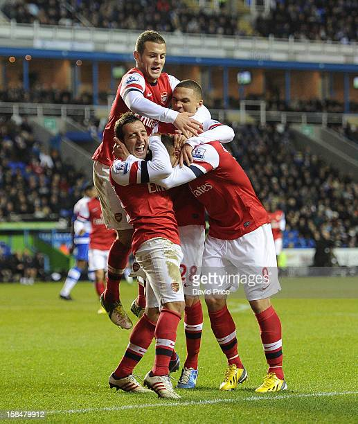 Santi Cazorla celebrates scoring his third goal for Arsenal with Lukas Podolski and his team mates during the Barclays Premier League match between...