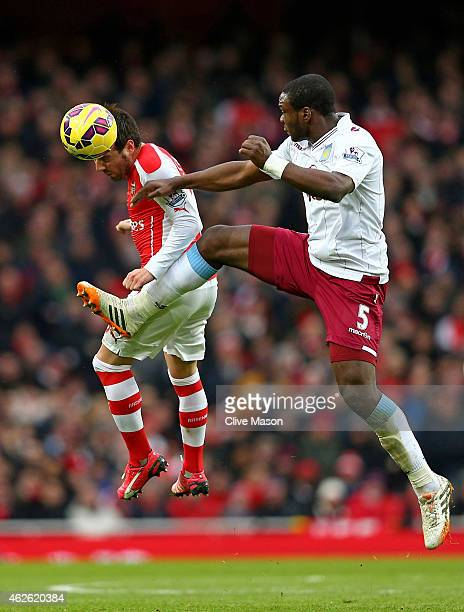 Santi Cazorla of Arsenal and Jores Okore of Aston Villa compete for the ball during the Barclays Premier League match between Arsenal and Aston Villa...