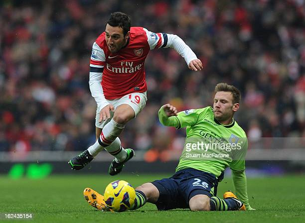 Santi Cazorla of Arsenal breaks past Andreas Weimann of Aston Villa during the Barclays Premier League match between Arsenal and Aston Villa at...