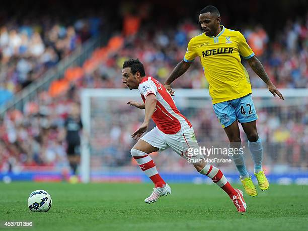 Santi Cazorla of Arsenal breaks past Jason Puncheon of Crystal Palace during the Barclays Premier League match between Arsenal and Crystal Palace at...