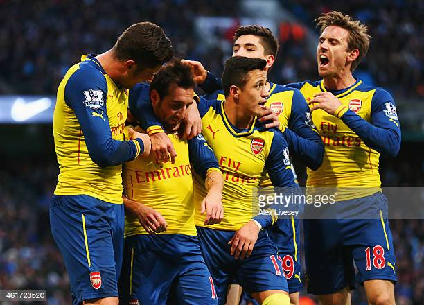 Santi Cazorla of Arsenal celebrates with team mates as he scores their first goal from a penalty during the Barclays Premier League match between...
