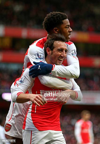 Santi Cazorla of Arsenal celebrates with teammate Chuba Akpom of Arsenal after scoring his team's fourth goal from the penalty spot during the...