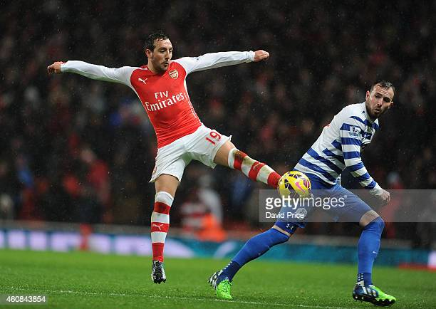 Santi Cazorla of Arsenal controls the ball as Jordan Mutch of QPR looks on during the match between Arsenal and Queens Park Rangers at Emirates...