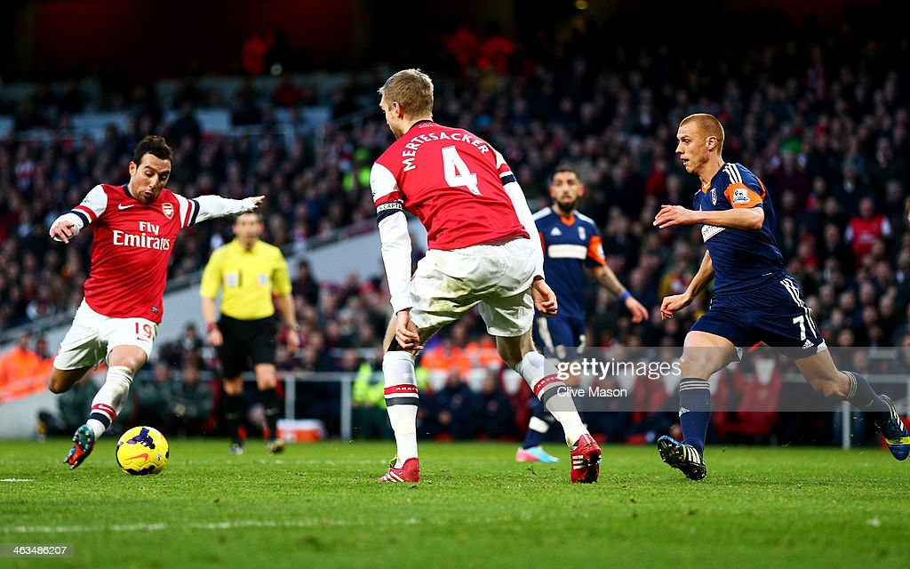 Santi Cazorla of Arsenal (L) controls the ball before scoring their second goal during the Barclays Premier League match between Arsenal and Fulham at Emirates Stadium on January 18, 2014 in London, England.