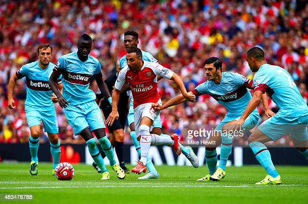 Santi Cazorla of Arsenal evades Cheikhou Kouyate and James Tomkins of West Ham United during the Barclays Premier League match between Arsenal and...