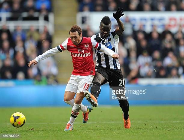 Santi Cazorla of Arsenal is challenged by Cheick Tiote of Newcastle during the Barclays Premier League match between Newcastle United and Arsenal at...