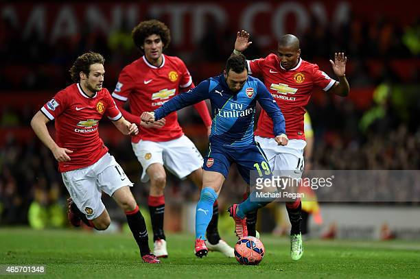 Santi Cazorla of Arsenal is closed down by Daley Blind Marouane Fellaini and Ashley Young of Manchester United during the FA Cup Quarter Final match...