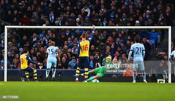 Santi Cazorla of Arsenal shoots past goalkeeper Joe Hart of Manchester City to score their first goal from a penalty during the Barclays Premier...