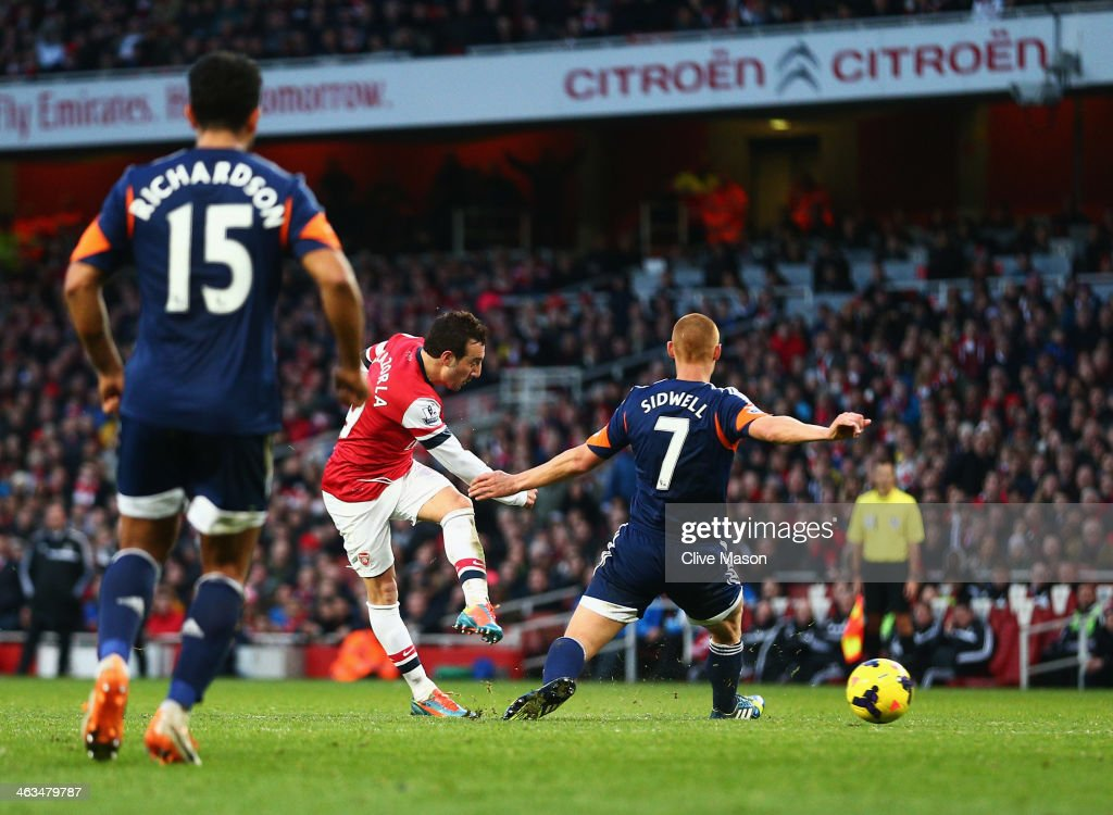 Santi Cazorla of Arsenal (C) shoots past Steve Sidwell of Fulham to score their second goal during the Barclays Premier League match between Arsenal and Fulham at Emirates Stadium on January 18, 2014 in London, England.