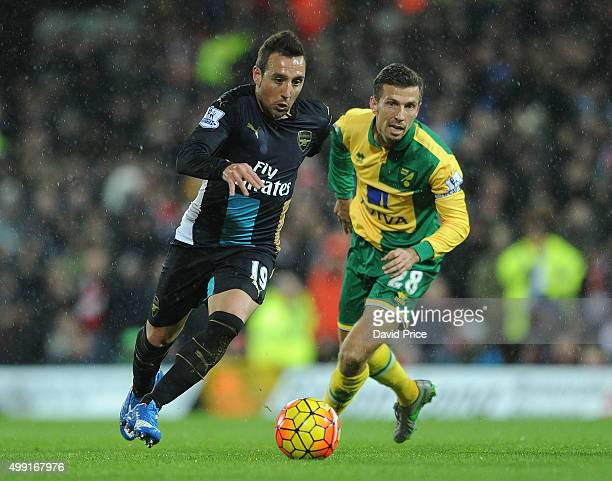 Santi Cazorla of Arsenal skips round Gary O'Neil of Norwich during the Barclays Premier League match between Norwich City and Arsenal at Carrow Road...