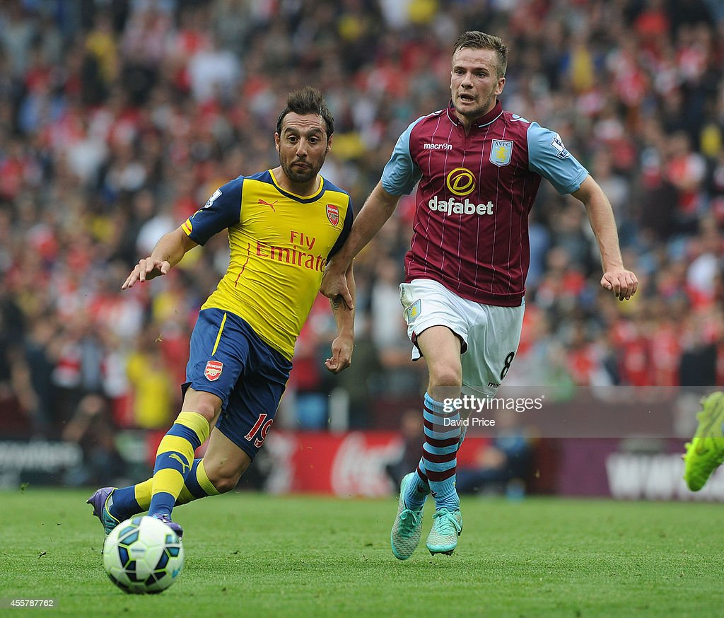 Santi Cazorla of Arsenal under pressure from Tom Cleverley of Villa during the Barclays Premier League match between Aston Villa and Arsenal at Villa Park on September 20, 2014 in Birmingham, England.