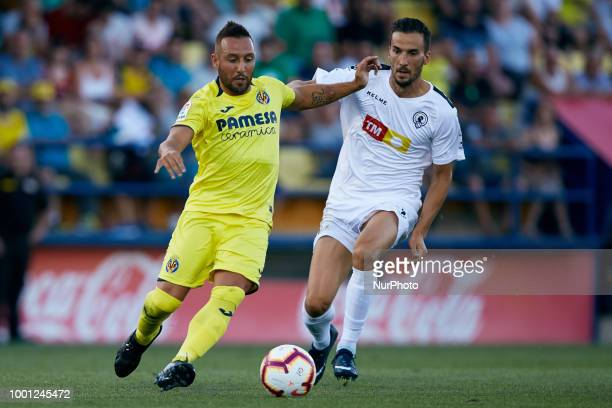 Santi Cazorla of Villarreal CF competes for the ball with Oscar Diaz of Hercules CF during the PreSeason Friendly match between Villarreal CF and...