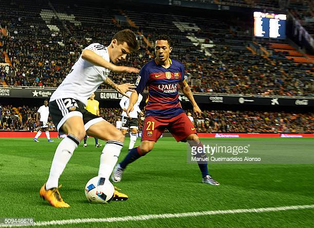 Santi Mina of Valencia competes for the ball with Adriano of Barcelona during the Copa del Rey Semi Final second leg match between Valencia CF and FC...