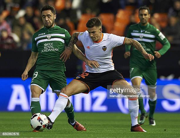 Santi Mina of Valencia competes for the ball with Carl Medjani of Leganes during the Copa del Rey Round of 16 match between Valencia CF and CD...