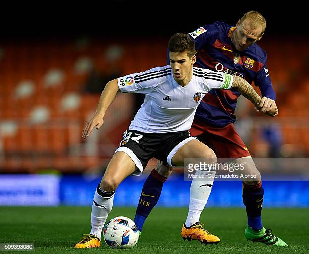Santi Mina of Valencia competes for the ball with Jeremy Mathieu of Barcelona during the Copa del Rey Semi Final second leg match between Valencia CF...
