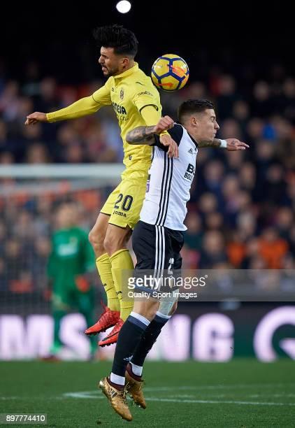 Santi Mina of Valencia competes for the ball with Roberto Soriano of Villarreal during the La Liga match between Valencia and Villarreal at Mestalla...