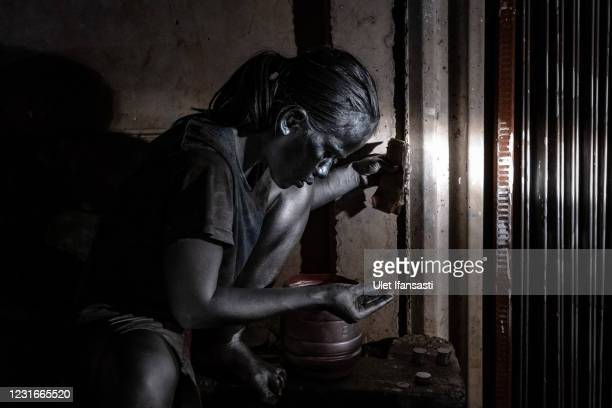 """Santi , wearing silver paint counting money after begging on the street on March 10, 2021 in Depok, Indonesia. 'Silver Men', called """"Manusia Silver""""..."""