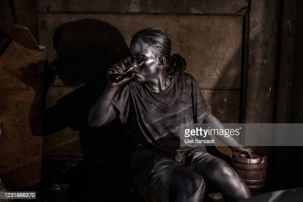 """Santi , wearing silver paint drinking as beg on the street on March 10, 2021 in Depok, Indonesia. 'Silver Men', called """"Manusia Silver"""" in Indonesian..."""