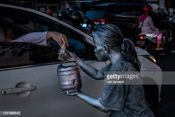 Santi , wearing silver paint receive money from a driver as begging on the street on March 10, 2021 in Depok, Indonesia. 'Silver Men', called...