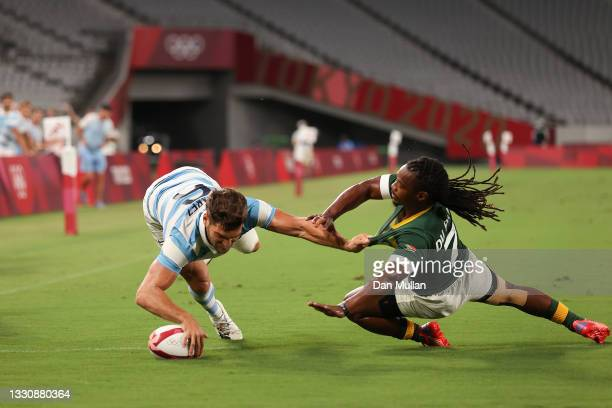 Santiago Alvarez of Team Argentina scores a try while getting tackled by Branco du Preez of Team South Africa during the Rugby Sevens Men's...