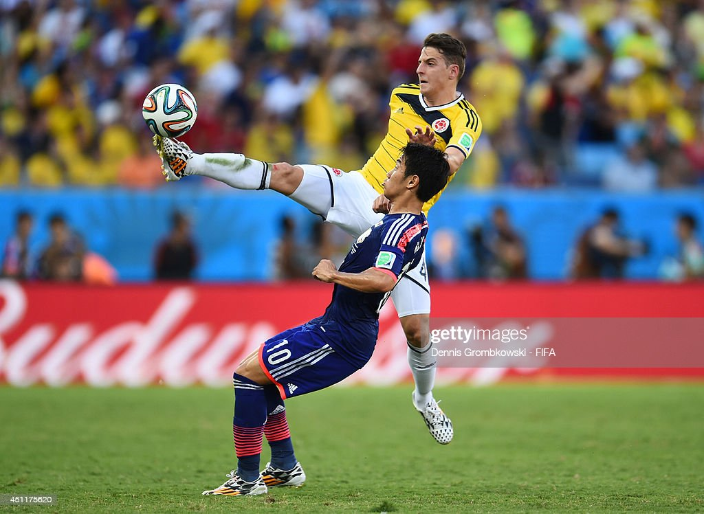 Santiago Arias of Colombia and Shinji Kagawa of Japan compete for the ball during the 2014 FIFA World Cup Brazil Group C match between Japan and Colombia at Arena Pantanal on June 24, 2014 in Cuiaba, Brazil.