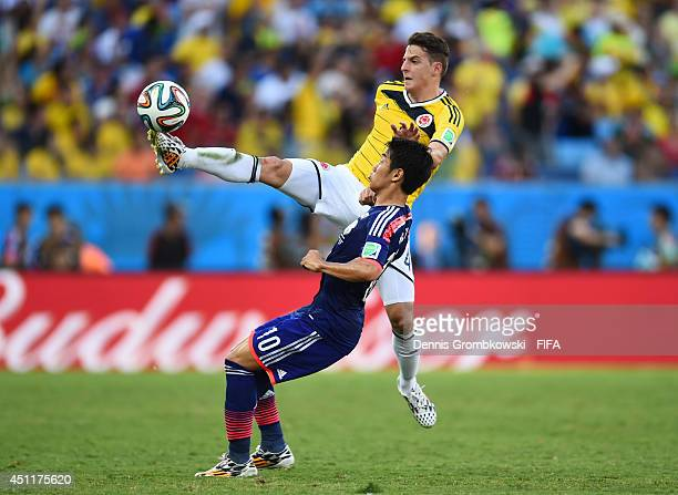 Santiago Arias of Colombia and Shinji Kagawa of Japan compete for the ball during the 2014 FIFA World Cup Brazil Group C match between Japan and...