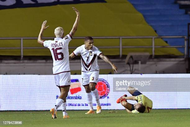 Santiago Arias of Colombia reacts after suffering an injury as Darwin Machis and Roberto Rosales of Venezuela ask to stop the play during a match...
