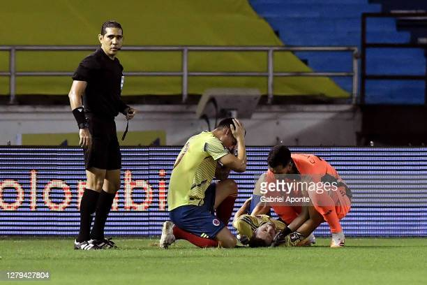 Santiago Arias of Colombia reacts after suffering an injury as teammates James Rodríguez and Camilo Vargas help him during a match between Colombia...