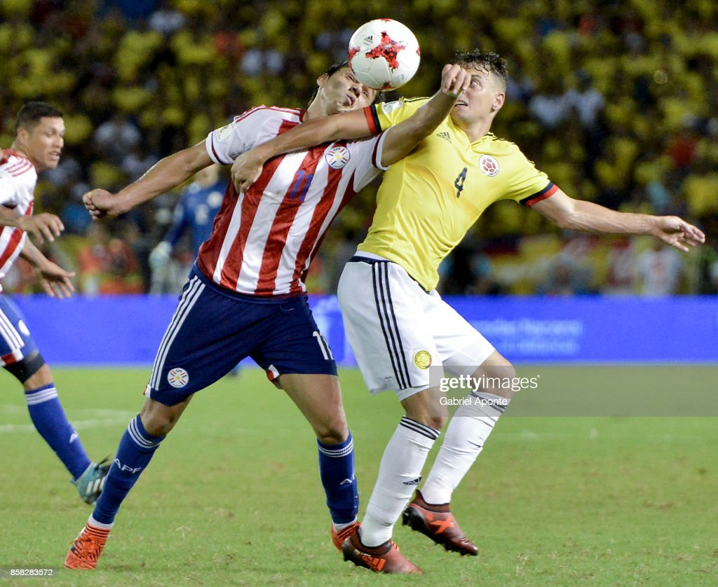 Santiago Arias of Colombia struggles for the ball with Angel Romero of Paraguay during a match between Colombia and Paraguay as part of FIFA 2018 World Cup Qualifiers at Metropolitano Roberto Melendez Stadium on October 05, 2017 in Barranquilla, Colombia.