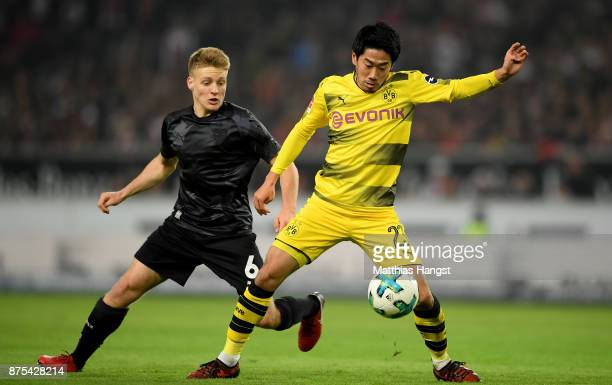 Santiago Ascacibar of Stuttgart is challenged by Shinji Kagawa of Dortmund during the Bundesliga match between VfB Stuttgart and Borussia Dortmund at...
