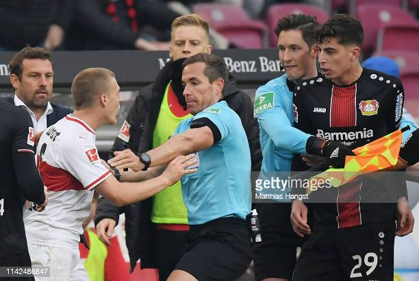 Santiago Ascacibar of VfB Stuttgart clashes with the referee Tobias Stieler after being sent off for spitting on Kai Havertz of Leverkusen during the...