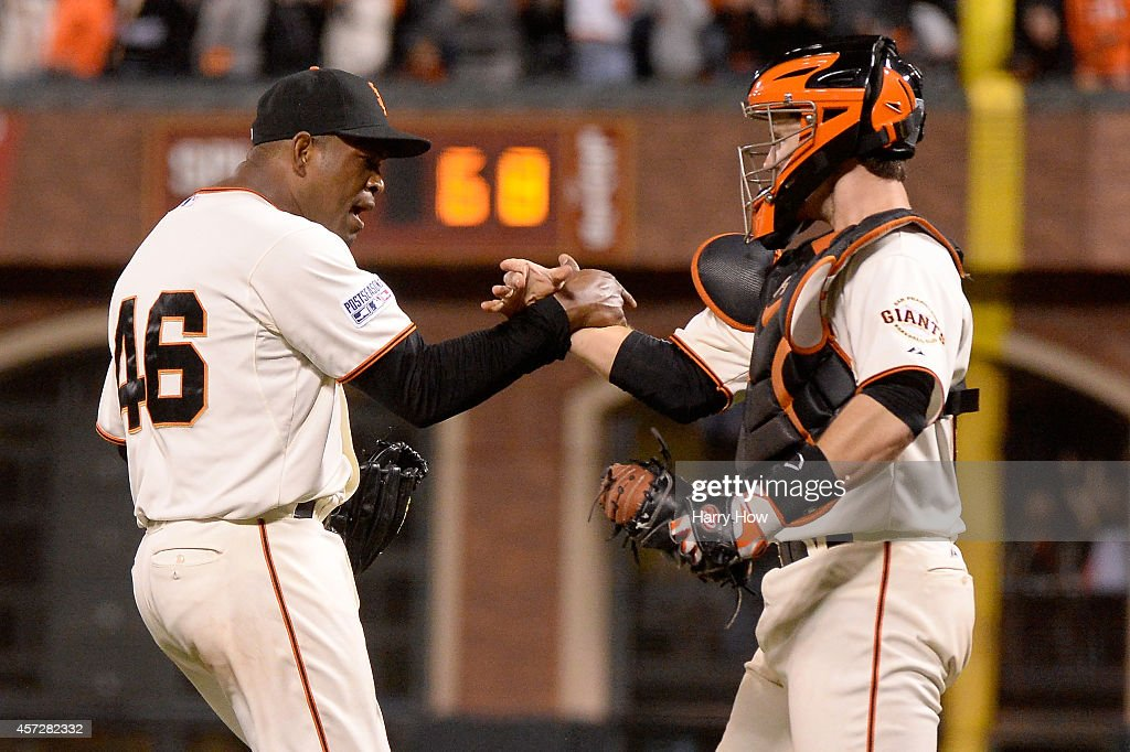 Santiago Casilla #46 and Buster Posey #28 of the San Francisco Giants celebrate after getting the final out in the ninth inning against the St. Louis Cardinals during Game Four of the National League Championship Series at AT&T Park on October 15, 2014 in San Francisco, California.